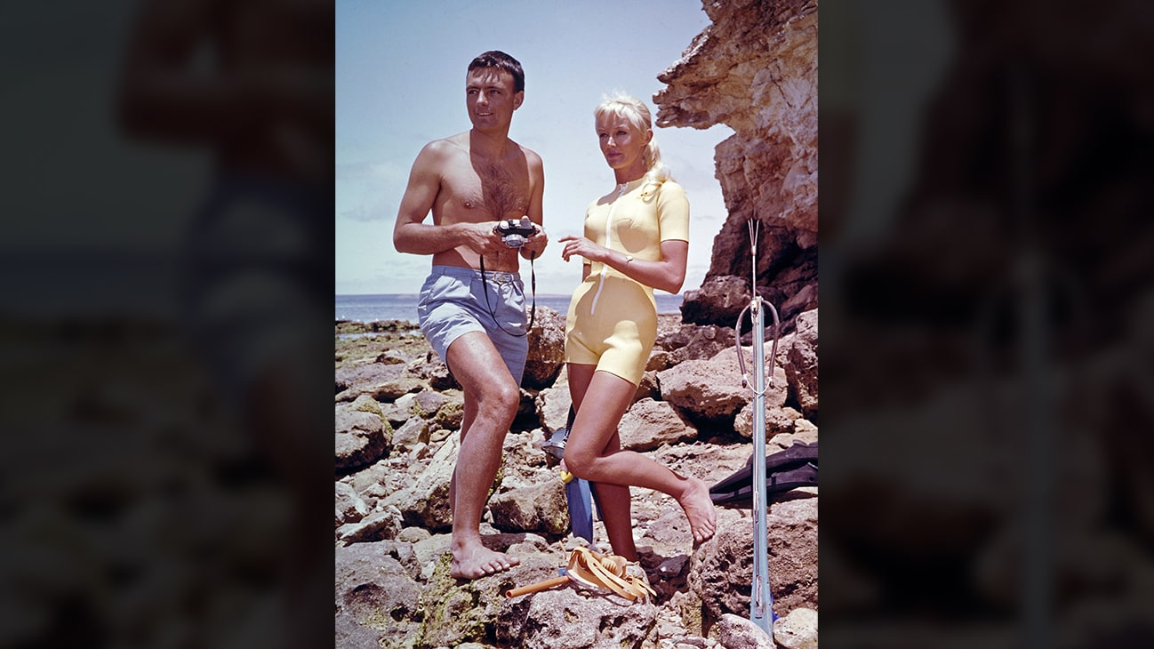 Ron & Valerie Taylor with spearfishing equipment standing on rocks in 1962. (photo credit: Ron & Valerie Taylor)