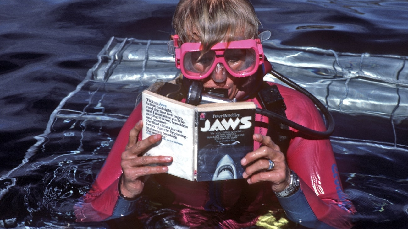 Valerie Taylor in scuba gear reading the Jaws book on top a shark cage in 1982. (photo credit: Ron & Valerie Taylor)