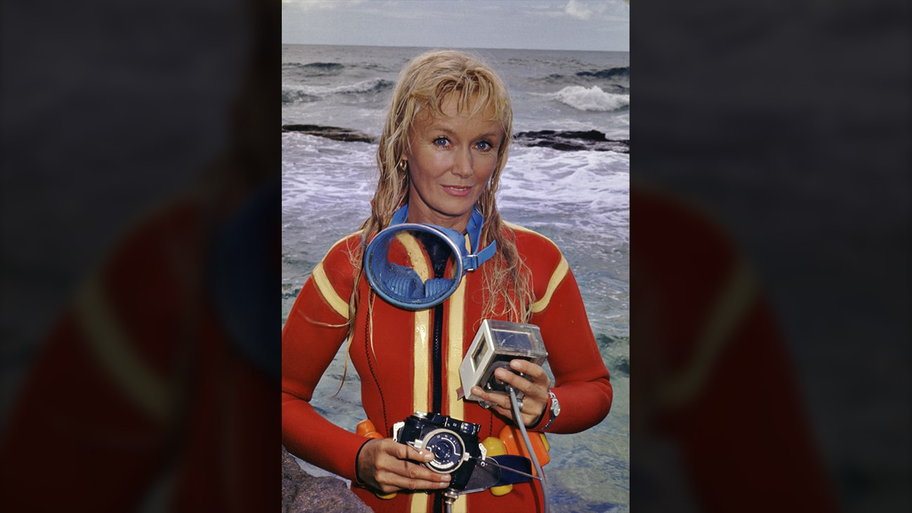 Valerie Taylor in red wetsuit posing with camera equipment. (photo credit: Ron & Valerie Taylor)