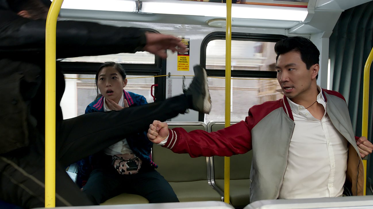 Shang-Chi (Simu Liu) and Katy (Awkwafina) fight a kicking enemy on a subway from the Marvel Studios movie Shang-Chi and the Legend of the Ten Rings.