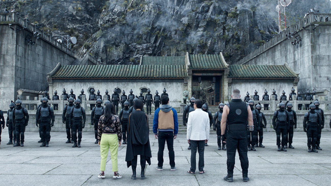 Shang-Chi (Simu Liu) and Katy (Awkwafina) stand in a stone courtyard facing a group of soldiers. There is a building and a mountain in the background. From Marvel Studios' Shang-Chi and The Legend of the Ten Rings.