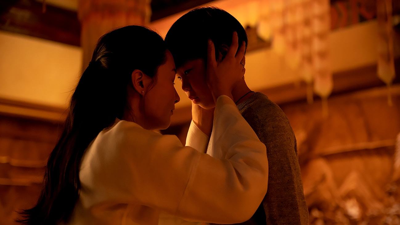 A mother cradles a young boy's head towards hers while kneeling from Marvel Studios' Shang-Chi and The Legend of the Ten Rings.