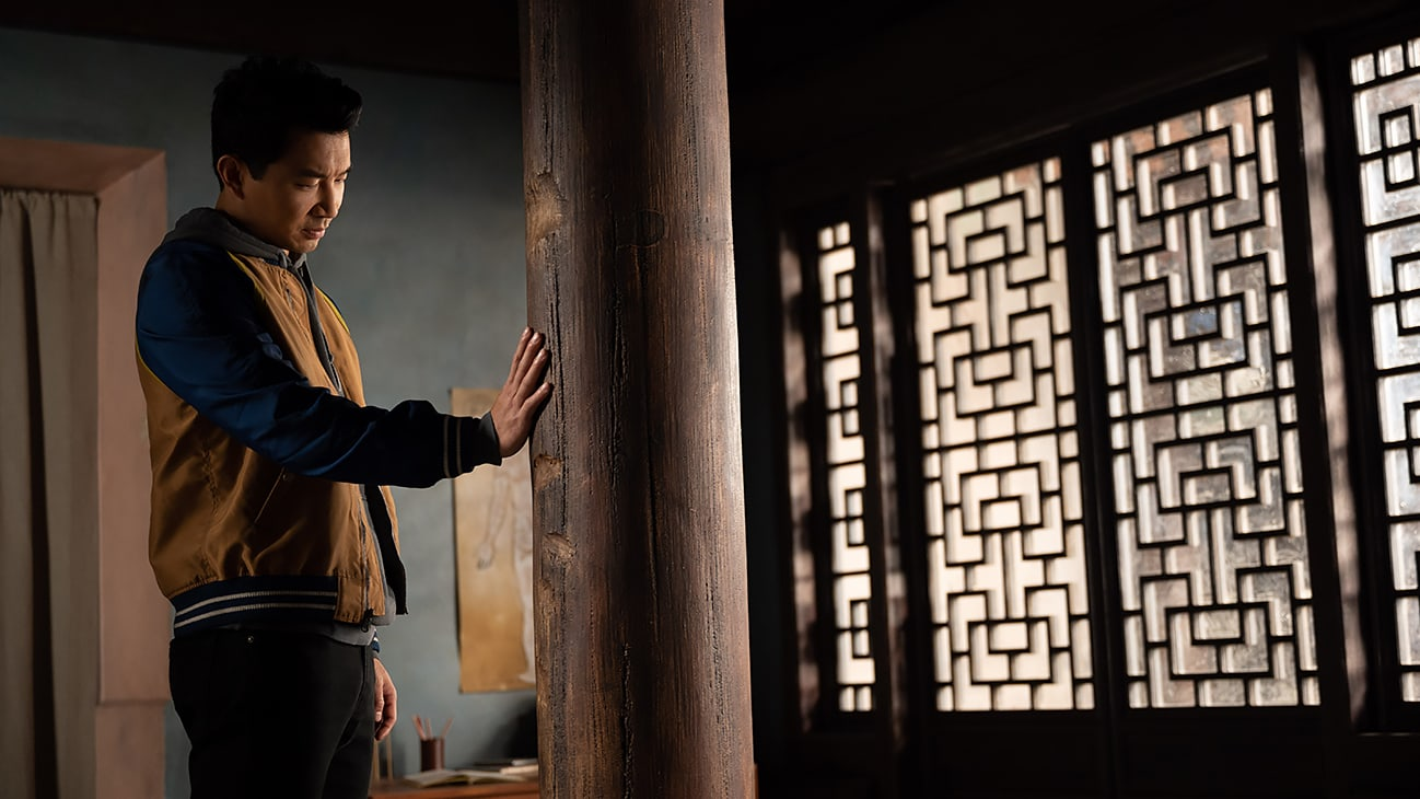 Shang-Chi (Simu Liu) places a hand on a large wooden pillar from Marvel Studios' Shang-Chi and The Legend of the Ten Rings.