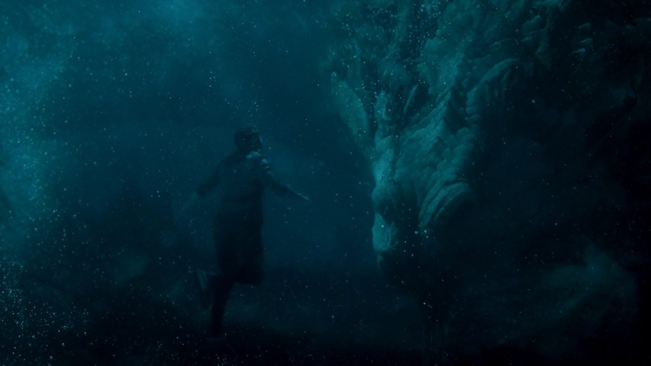 A person swimming underwater stares at a large head of a giant creature from Marvel Studios' Shang-Chi and The Legend of the Ten Rings.