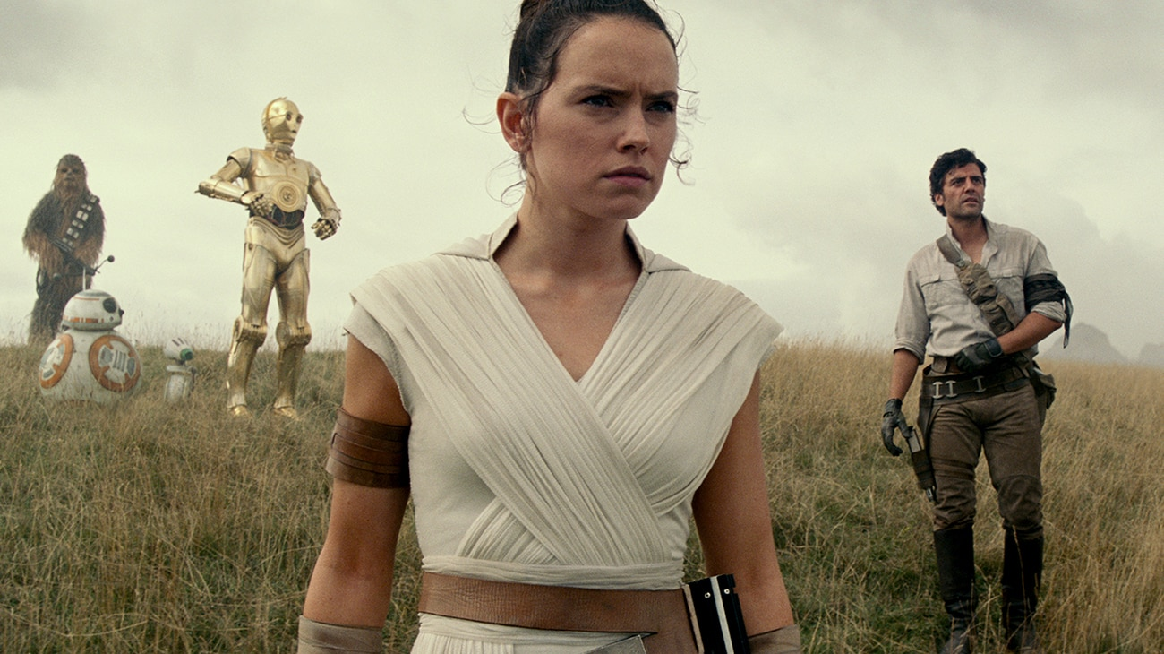 """Daisy Ridley as Rey, Oscar Isaac as Poe Dameron, Anthony Daniels as C-3PO, BB-8, and Joonas Suotamo as Chewbacca standing on a grassy hill in """"Star Wars: The Rise of Skywalker"""""""