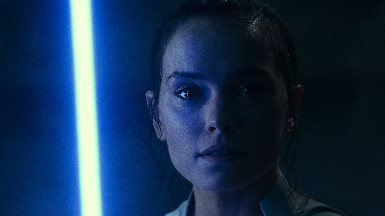 """Daisy Ridley as Rey in the dark, her face glowing from the light of a blue light saber, in """"Star Wars: The Rise of Skywalker"""""""