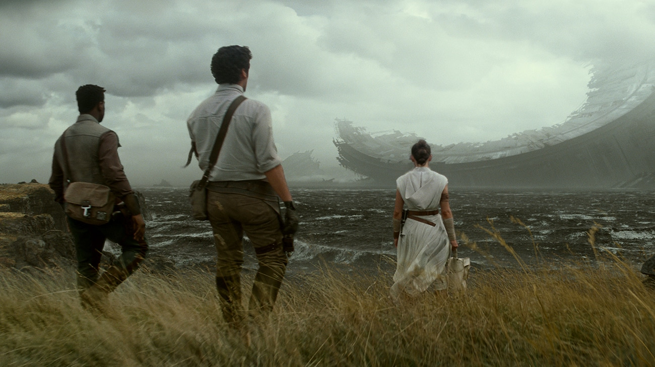 """The backs of Daisy Ridley as Rey, Oscar Isaac as Poe Dameron, and John Boyega as Finn looking out onto the water at a wrecked ship in """"Star Wars: The Rise of Skywalker"""""""
