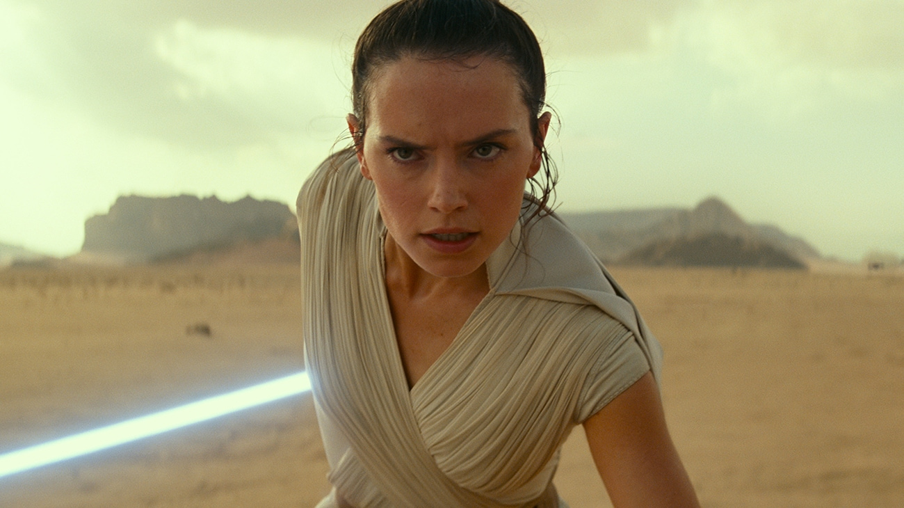 """Daisy Ridley as Rey, in a ready for action pose and holding her blue light saber while standing in the desert, in """"Star Wars: The Rise of Skywalker"""""""