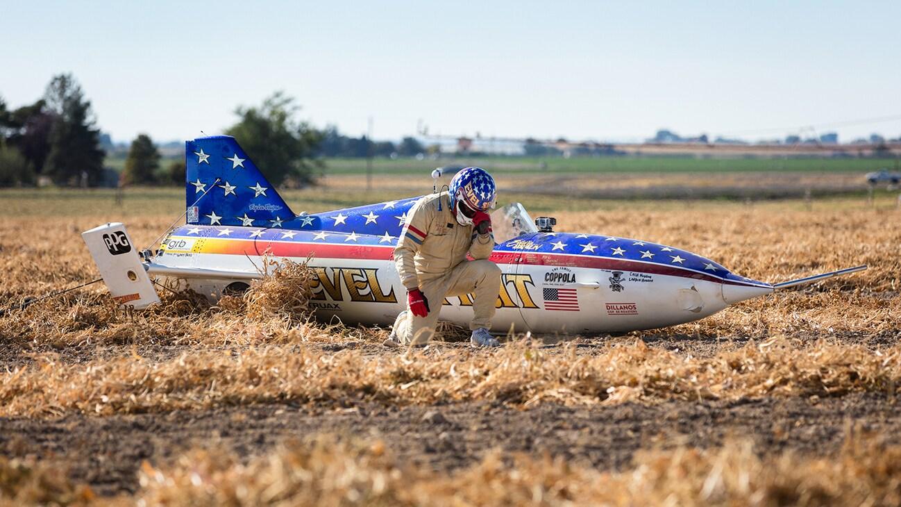 Image of Eddie Braun kneeling next to his rocket from the Disney+ Originals movie Stuntman. (Disney/ Steve Dondero)