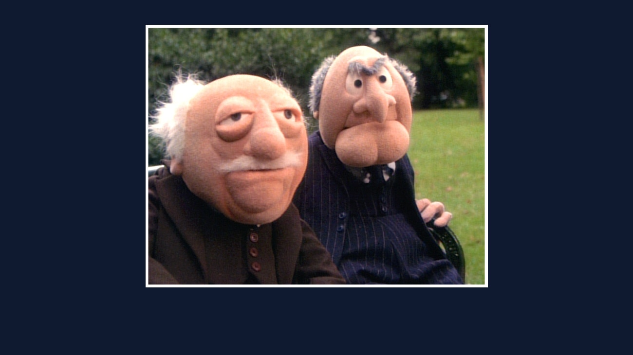 Statler and Waldorf sitting on a park bench from the Disney movie The Great Muppet Caper.