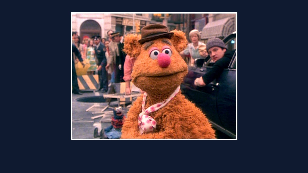 Fozzie standing next to a car in the street from the Disney movie The Great Muppet Caper.