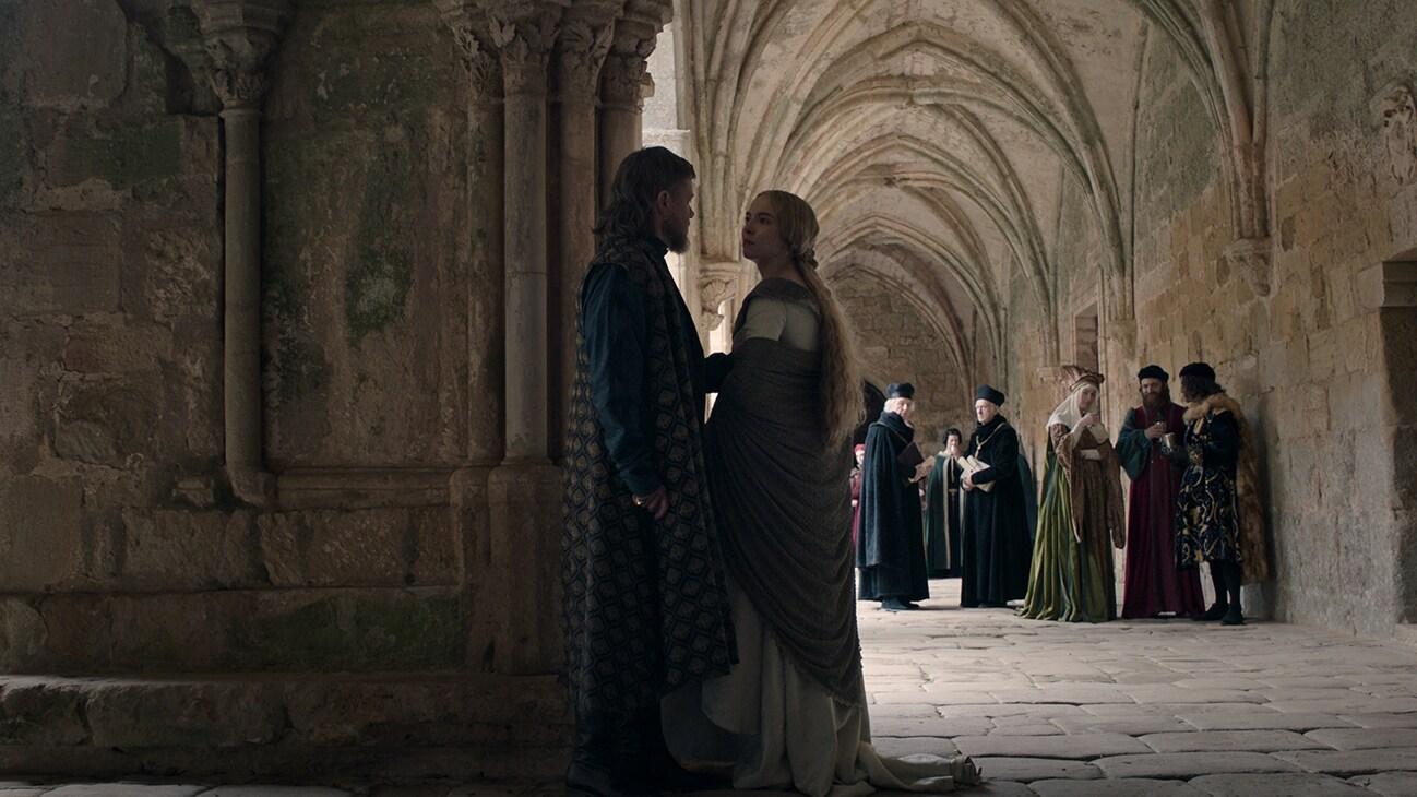 Jean de Carrouges (actor Matt Damon) and Marguerite de Carrouges (actor Jodie Comer) standing in a stone passageway from the 20th Century Studios movie The Last Duel.