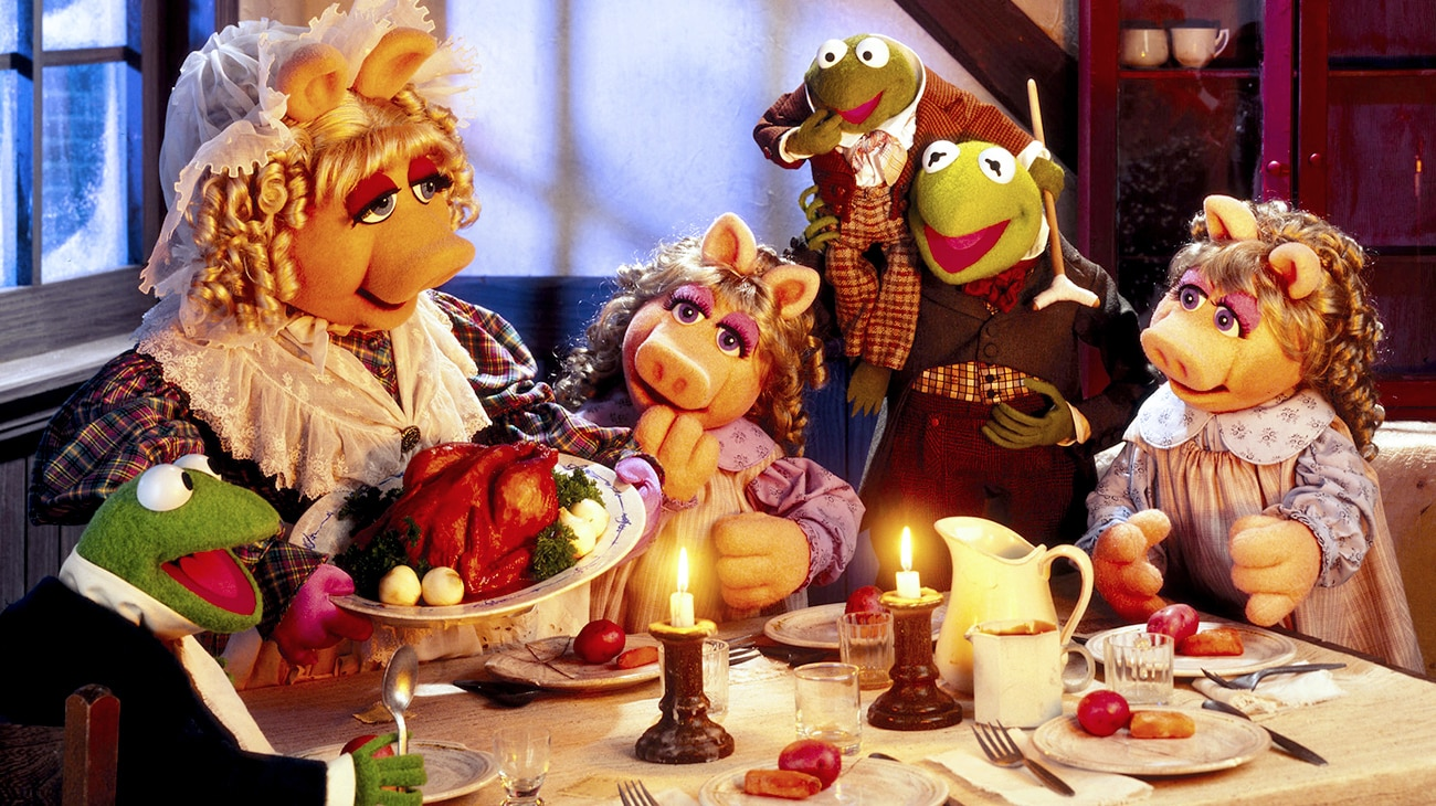 Kermit the Frog as Bob Cratchit (voice of Steve Whitmire), Tiny Tim Cratchit (voice of Jerry Nelson), and Miss Piggy as Emily Cratchit (voice of Frank Oz) at the dinner table in the Disney movie The Muppet Christmas Carol.