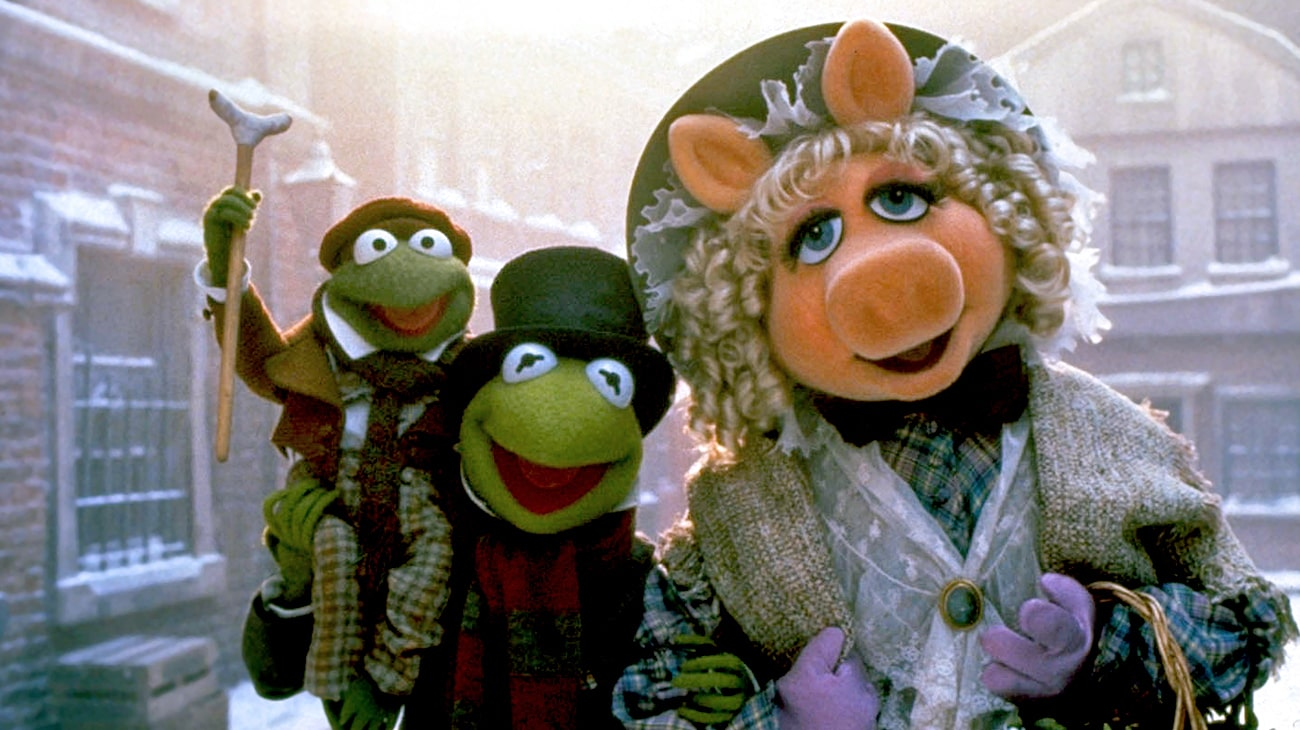 Kermit the Frog as Bob Cratchit (voice of Steve Whitmire), Tiny Tim Cratchit (voice of Jerry Nelson), and Miss Piggy as Emily Cratchit (voice of Frank Oz) in the Disney movie The Muppet Christmas Carol.