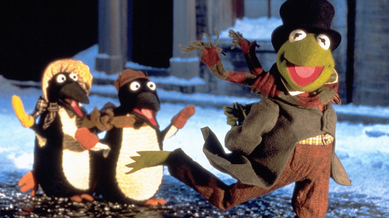 Kermit the Frog as Bob Cratchit (voice of Steve Whitmire) walking with penguins (voice of Jerry Nelson) from the Disney movie The Muppet Christmas Carol.