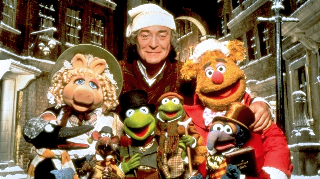 Ebenezer Scrooge (Michael Caine), The Great Gonzo as Charles Dickens (voice of Dave Goelz), Kermit the Frog as Bob Cratchet (voice of Steve Whitmire), Tiny Tim Cratchit (voice of Jerry Nelson), Miss Piggy as Emily Cratchit (voice of Frank Oz), and Fozzie Bear as Fozziwig (voice of Frank Oz), and Rizzo the Rat (voice of Steve Whitmire), in The Muppet Christmas Carol (1992)