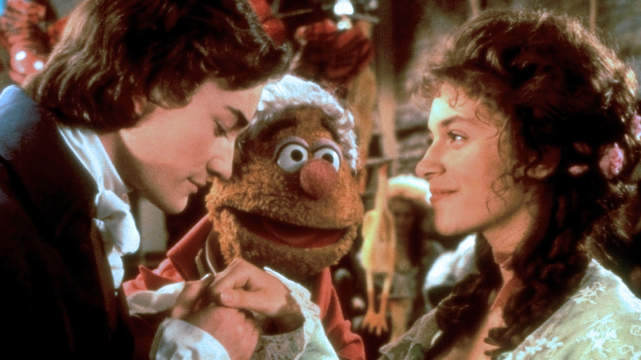 Fozzie Bear as Fozziwig (voice of Frank Oz), young Ebenezer Scrooge (Raymond Coulthard), and Belle (Meredith Braun) from the Disney movie The Muppet Christmas Carol.