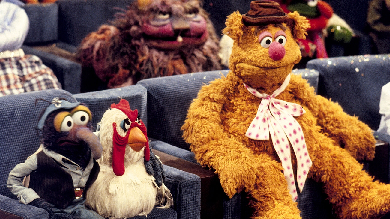Camilla the chicken and Fozzie bear siting in a theater in The Muppet Movie