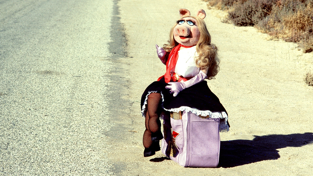 Miss Piggy sitting on a suitcase by the side of a road in The Muppet Movie