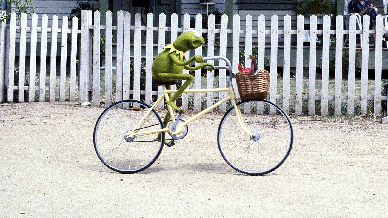 Kermit the Frog riding a bike in The Muppet Movie