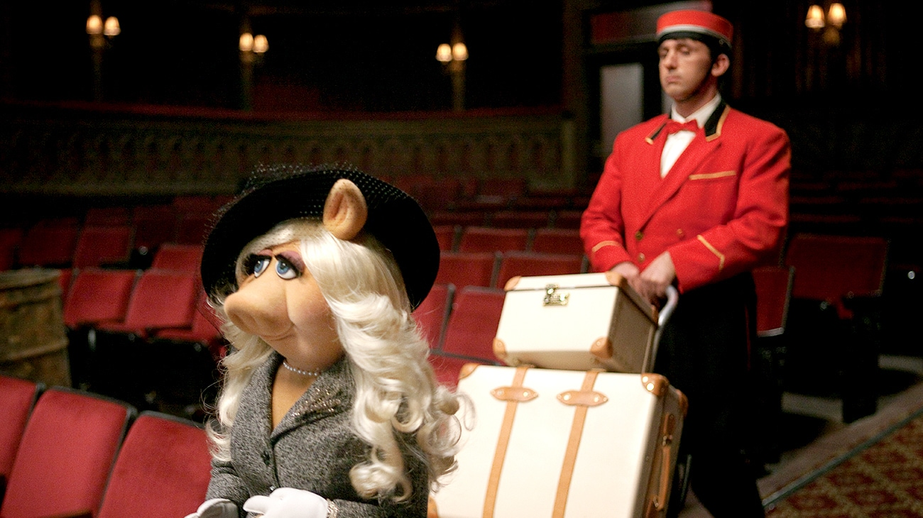 Miss Piggy arrives at the Muppet Theater with a bell boy carrying her luggage