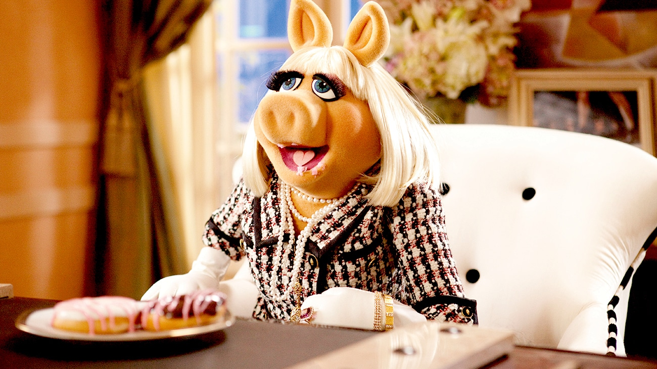 Mis Piggy voiced by Eric Jacobson sitting in front of a plate of doughnuts