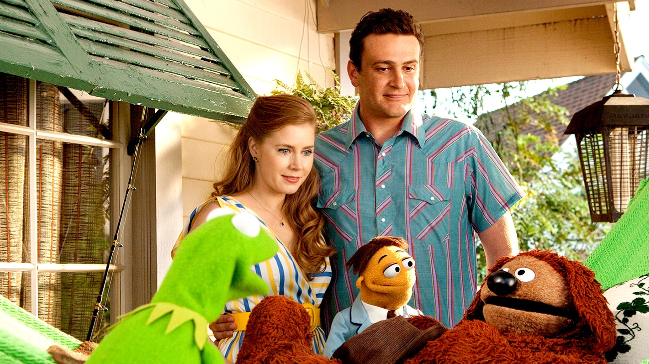 Jason Segel as Gary , Amy Adams as Mary, and Walter voiced by Peter Lintz talking to the muppets.