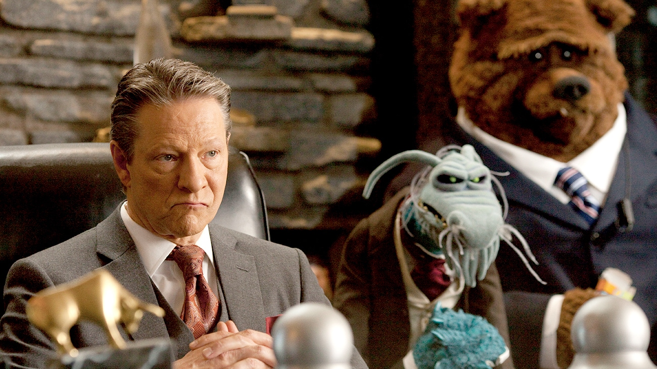 Chris Cooper as Tex Richman with sinister looking muppets at a desk