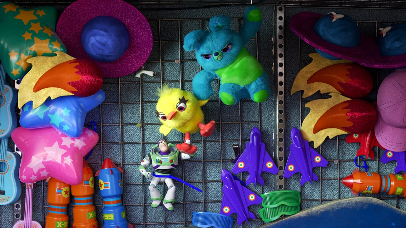 """Buzz, Ducky and Bunny hanging on the wall of a carnival game booth in the animated movie """"Toy Story 4"""""""