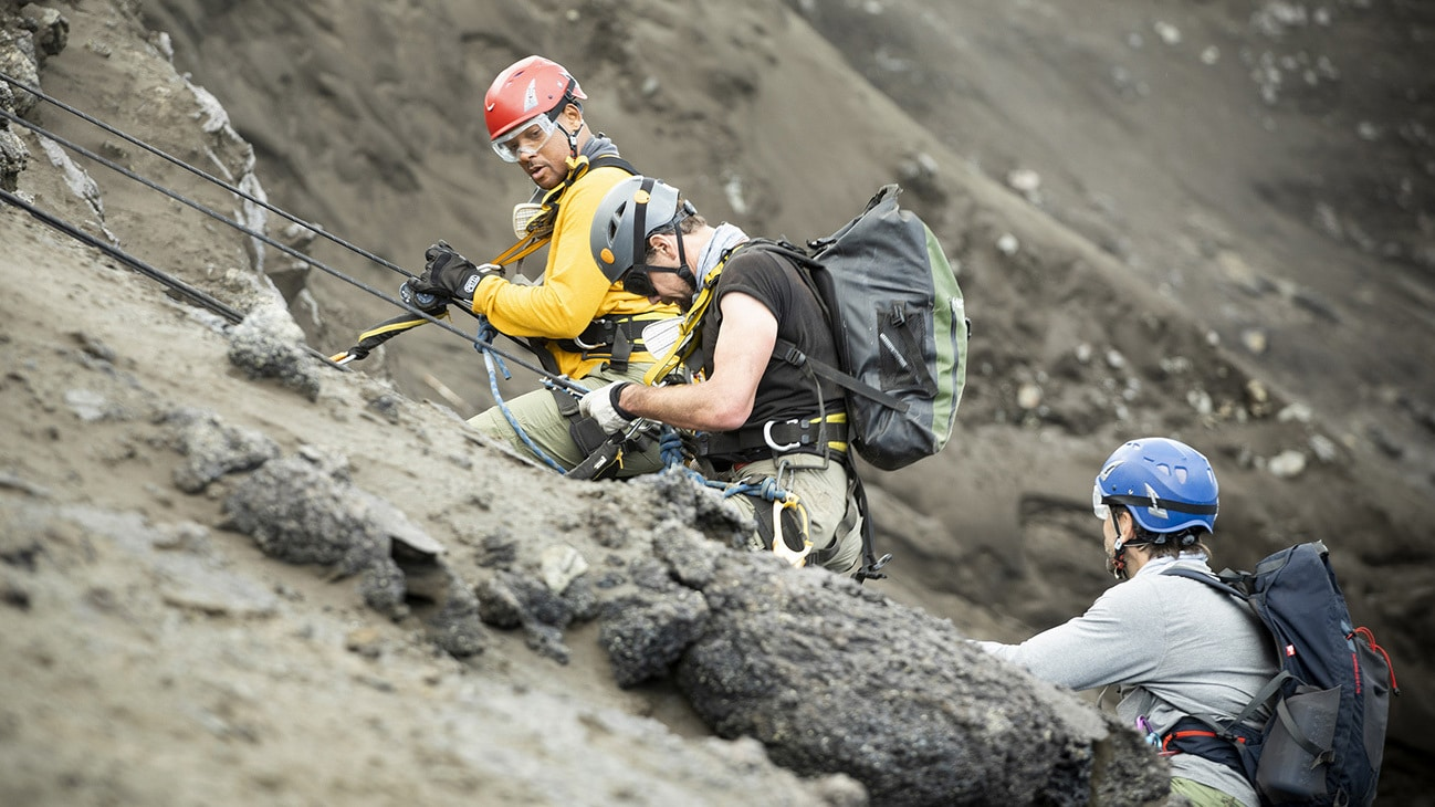 (L to R): Will Smith, Vulcanologist Jeff Johnson and Explorer Erik Weihenmayer descend into a volcano to install sensors. (National Geographic for Disney+/Kyle Christy)