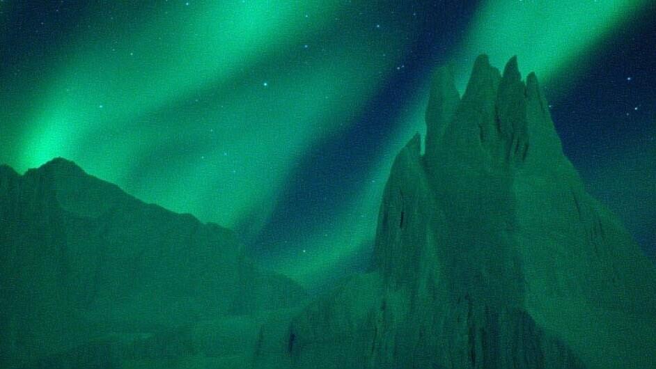 Glowing Green aurora borealis in the night sky