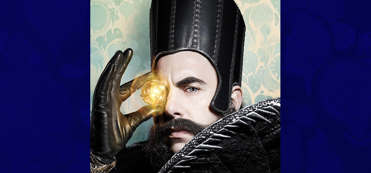 """Sacha Baron Cohen as Time holding a glowing ball in the movie """"Alice Through the Looking Glass"""""""