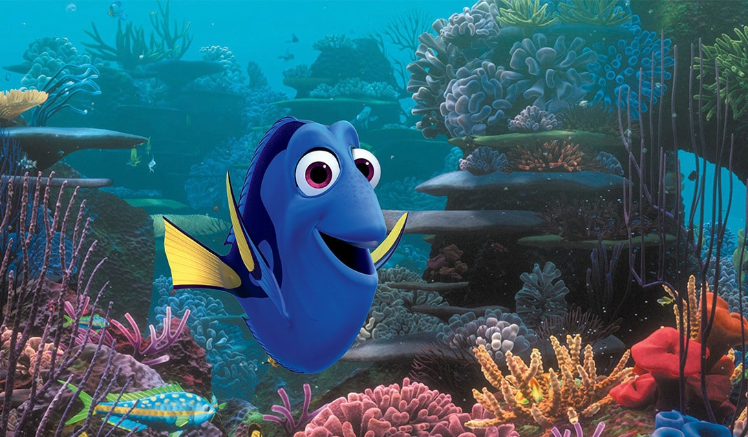 """A happy Dory (Ellen Degeneres) swimming in a coral reef in """"Finding Dory"""""""