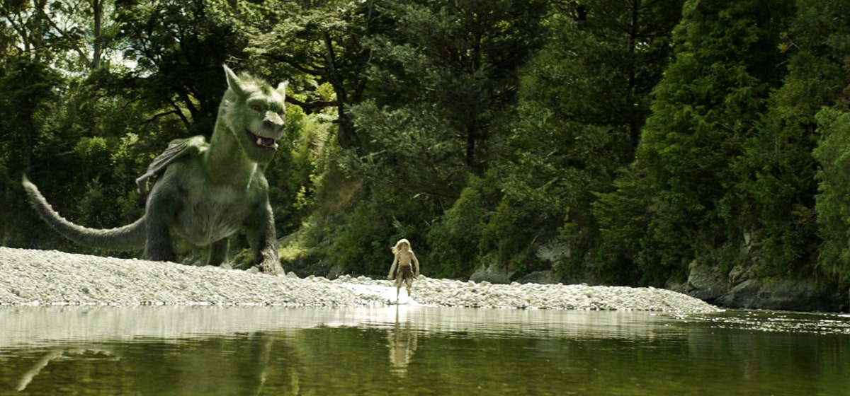 """Oakes Fegley (Pete) with the dragon playing near a lake in """"Pete's Dragon"""""""