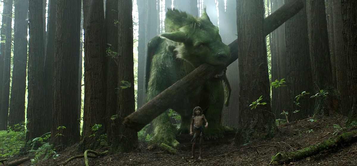 """Oakes Fegley (Pete) with the dragon walking in the woods in """"Pete's Dragon"""""""