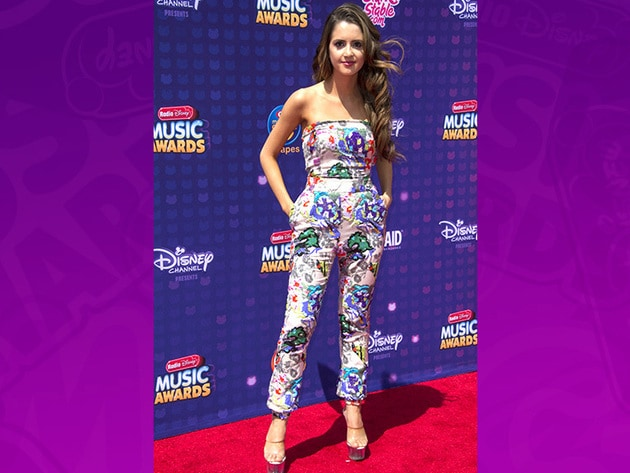 Laura Marano rocks a bright and colorful outfit on the red carpet. Get ready for her performance!