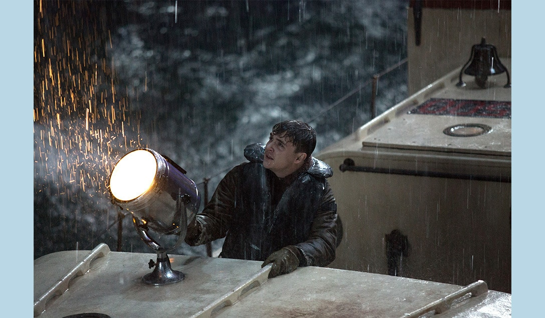 """Crew member on deck in the rain with a spot-light in the movie """"The Finest Hours"""""""