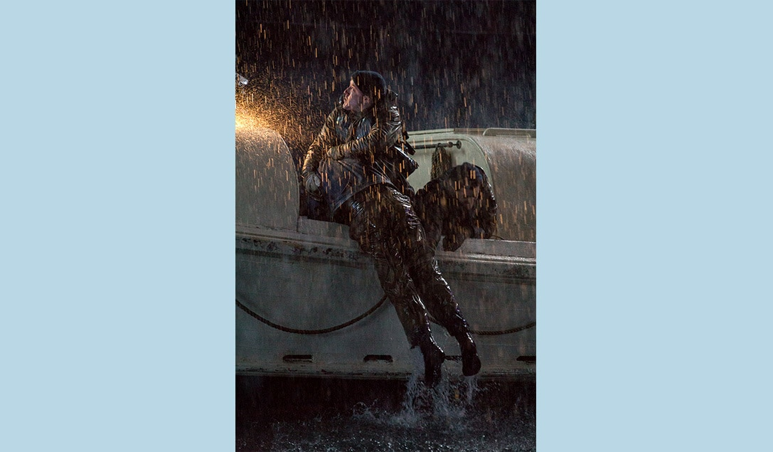 """A crew member pulls someone from the ocean and into the rescue boat in the movie """"The Finest Hours"""""""