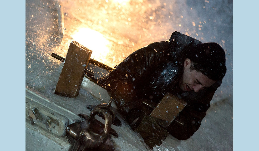 """Andy Fitzgerald (Kyle Gallner) desperately hanging on to the side of the ship in the movie """"The Finest Hours"""""""