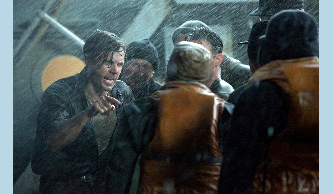 """Ray Sybert (Casey Affleck) standing in the rain with a group of men in """"The Finest Hours"""""""