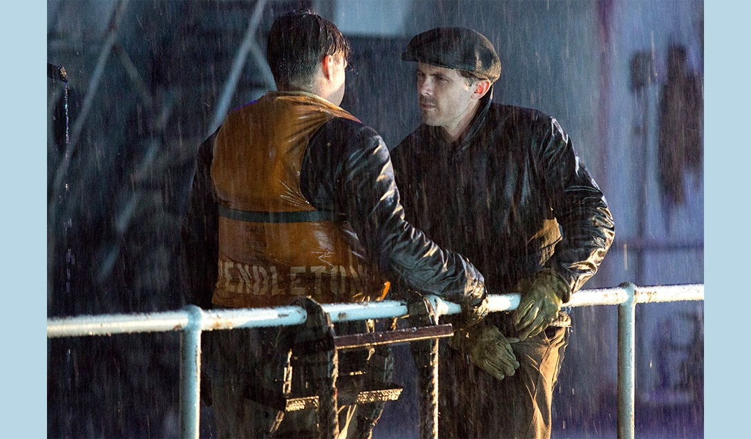 """Two men standing in the rain in the movie """"The Finest Hours"""""""