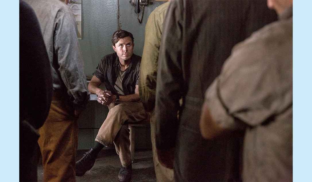 """Ray Sybert (Casey Affleck) seated at a table talking to the crew in the movie """"The Finest Hours"""""""