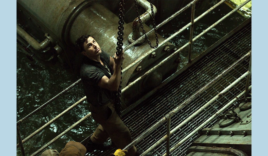 """Ray Sybert (Casey Affleck) in a flooded room hanging on to a chain in the movie """"The Finest Hours"""""""