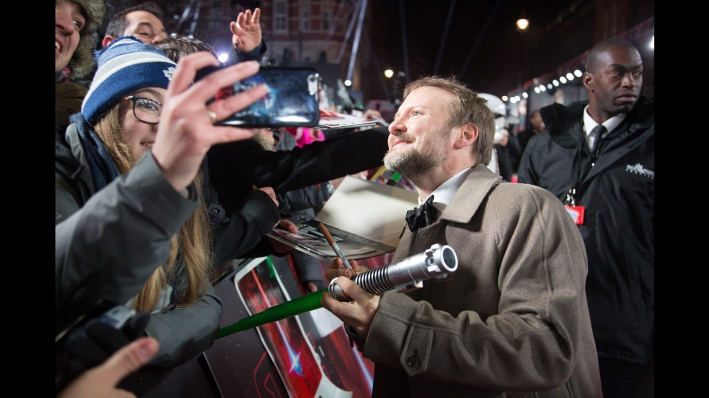Director Rian Johnson signing autographs on the red carpet at the Star: Wars The Last Jedi premiere