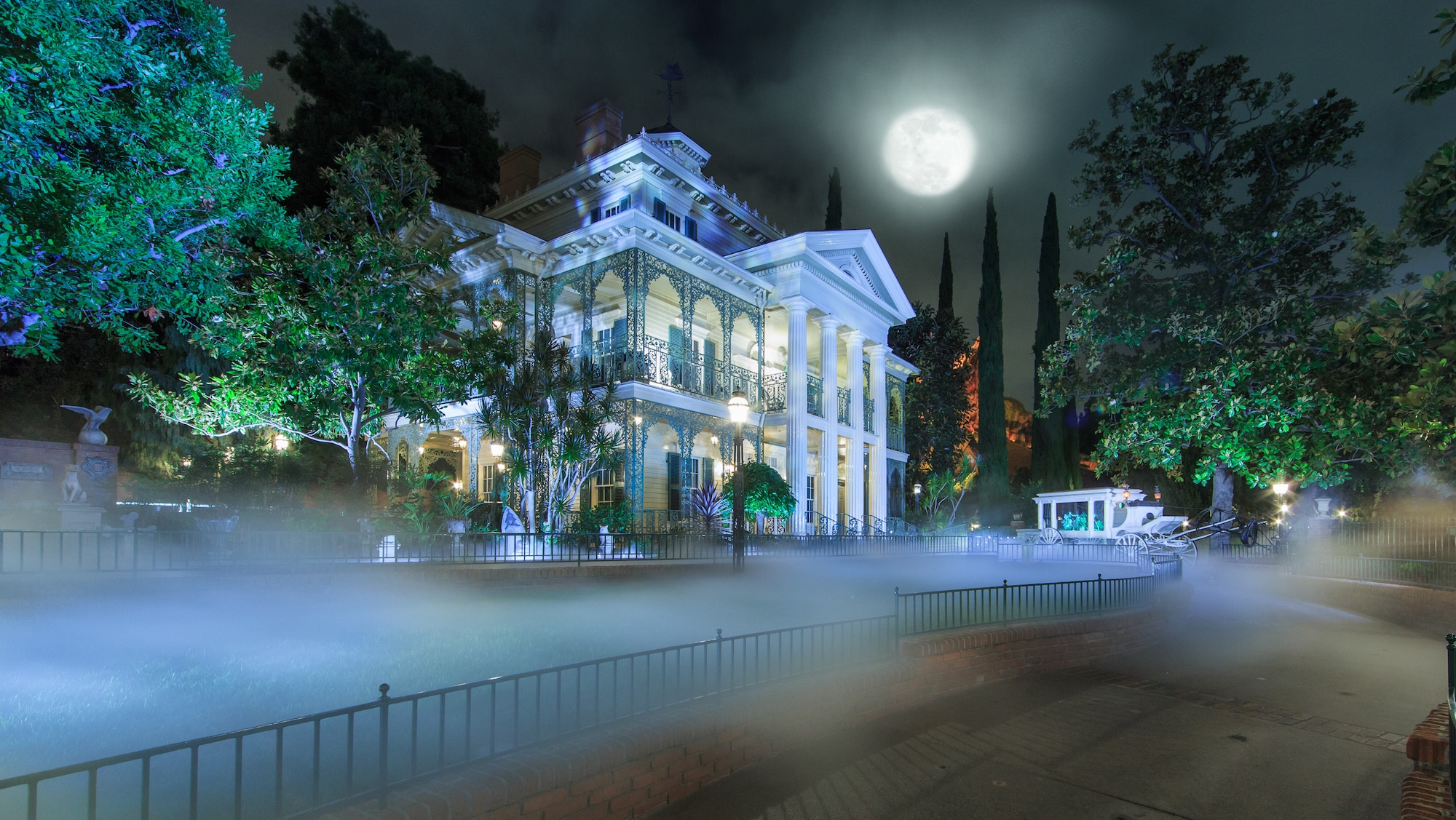 Image of the Haunted Mansion exterior at night.