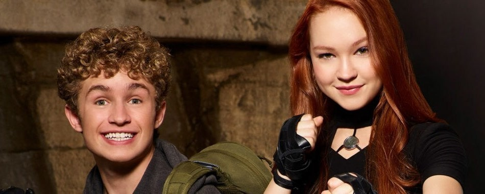 A teen boy with curly blonde hair wearing an army green backpack and all black clothing poses in a fighting pose with redheaded teen girl wearing a black top and gloves