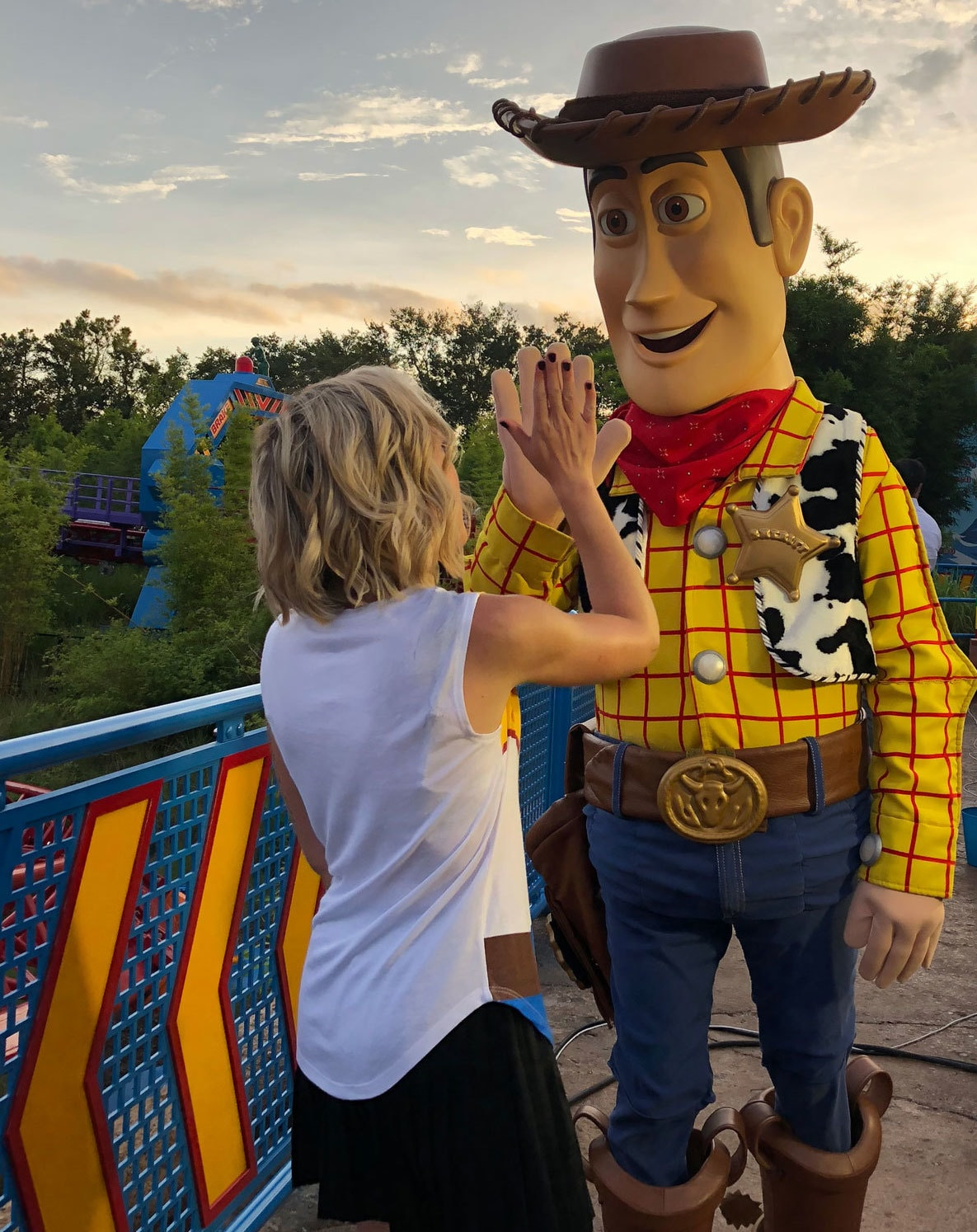 Oh My Disney Host Michelle Lema High fiving Woody in Toy Story Land at Walt Disney World