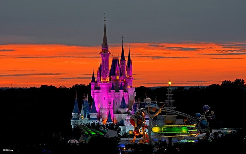Sunset behind  Walt Disney World Castle lit in purple
