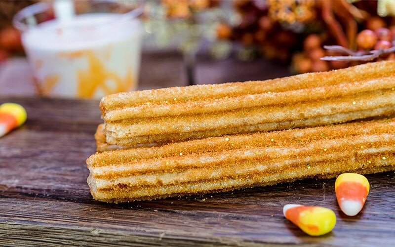 Orange Sugar Churros with candy corn sauce next to candy corn