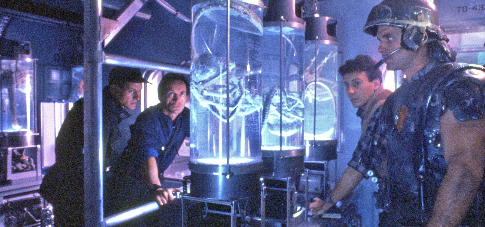 "Actors William Hope (as Lieutenant Gorman), Lance Henriksen: Bishop, Paul Reiser (as Burke) and Mark Rolston (as Private Drake) looking at a face hugger alien inside a tube from the movie ""Aliens"""